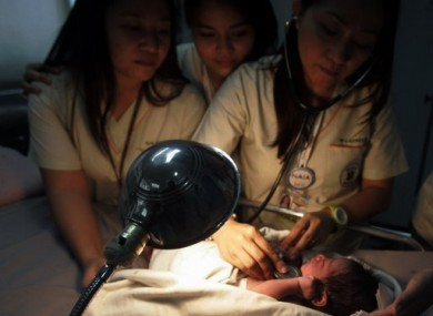 Nurses attend to a newborn baby found inside a bin at Manila's international airport, Philippines.