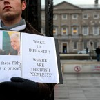 A campaigner stands outside Leinster House this morning, as news breaks of a Green Party press conference on the future of the government. Julien Behal/PA Wire