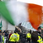 A Sinn Fein protestor waves a tricolour outside government buildings. (AP Photo/Peter Morrison)