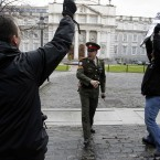 A Irish Army Military police officer confronts Sinn Fein protesters after they broke through the gates at government buildings. (AP Photo/Peter Morrison)