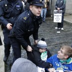 Gardaí remove Sinn Fein protesters from inside the gates of government buildings. (AP Photo/Peter Morrison)