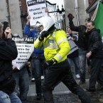A motorbike police officer holds back Sinn Fein protesters who broke through the gates at government buildings. (AP Photo/Peter Morrison)