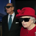 Queen Elizabeth II and the Duke of Edinburgh wearing 3D glasses to watch a display and pilot a JCB digger during a visit to the University of Sheffield Advanced Manufacturing Research centre.