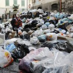A child makes her way through uncollected trash in Naples Italy, Monday, Nov. 22, 2010. 