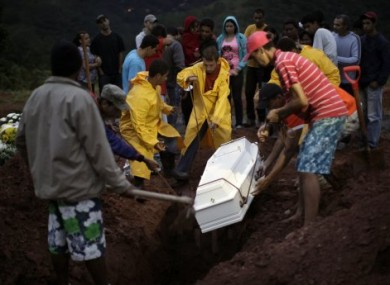 The casket of 9-year-old landslide victim Mauro Viana is lowered into the ground in Teresopolis, Brazil.