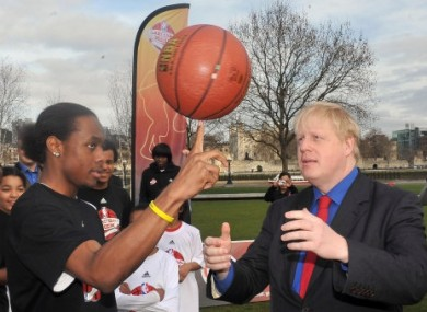 Mayor of London Boris Johnson learns basketball skills from Malcolm Jones, 16, of the Merton Hawks.