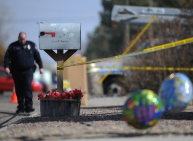 A Burlington police officer walks along the perimeter of the crime scene in Burlington, Colorado, on Wednesday.