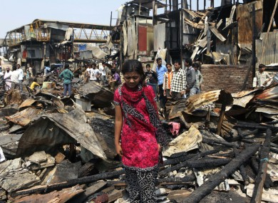 Slumdog Millionaire star Rubina Ali walks through the debris of her home in Mumbai, which was among 500 destroyed by fire on Friday night.