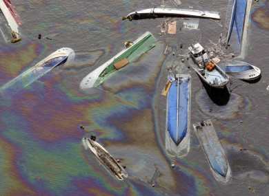 Vessels float on oil spilled water in Fudai in northern Japan.