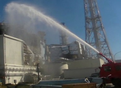 Image from the Japanese Defence Ministry showing a fire engine spraying water towards Reactor 3 on Friday.