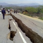 Residents walk along a road damaged by an earthquake in Tarlay, Shan state, Myanmar - dozens of people were killed in the quake yesterday.