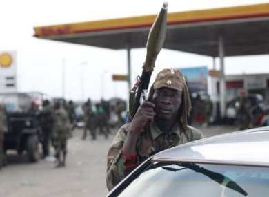 Soldiers loyal to Alassane Ouattara rest at a gas station in the Youpougon neighborhood, at the main northern entrance to Abidjan, Ivory Coast, Tuesday, April 5