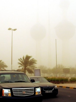 Motorists drive by the Kuwait Towers, nearly invisible in the background at just 300 meters during a severe sandstorm today.
