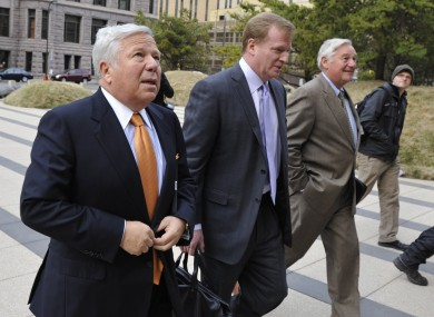 New England Patriots owner Robert Kraft, left, and NFL commissioner Roger Goodell, center, are escorted by NFL security as they arrive at Minneapolis courthouse for mediation talks.