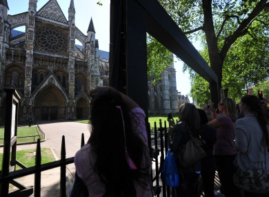 Tourists take photos of the exterior of Westminster Abbey. There will be nothing to stop guests doing the same inside the Abbey tomorrow
