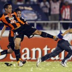 Luis Esqueda of Jaguares de Chiapas (Mexico) kicks a Colombia's Junior's fan who jumped onto the field during a Copa Libertadores football match on Thursday.