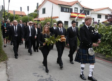 A lone bagpiper leads the funeral procession of Seve Ballesteros in Pedrena, Spain earlier today.