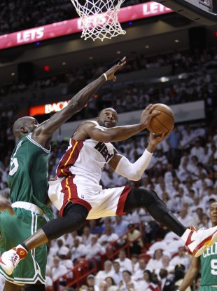 Miami Heat's Dwyane Wade, right, goes up for a shot against Boston Celtics' Kevin Garnett.