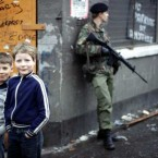 Local boys pose for the camera as a British soldier surveys the Falls Road in Belfast on the eve of Bobby Sands' funeral. Pic: Photocall Ireland