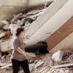 A woman walks by a collapsed building after the earthquake in Lorca, Spain which killed nine people. (AP Photo/Alberto Saiz)