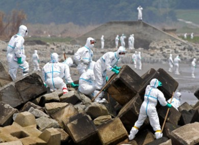 Fukushima police, wearing protective clothing, searching for missing people in the Fukushima Prefecture on 16 June, 2011.