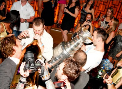 Zdeno Chara (right) drinks from the Stanley Cup as team mate Shawn Thornton necks a $100,000 bottle of bubbly.