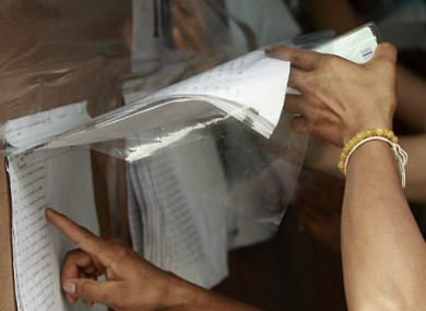 Holding an ID card in one hand, a Thai citizen browses lists of voters before casting absentee vote at a stadium in Bangkok, Thailand, Sunday, June 26,