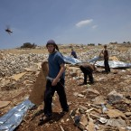 A Jewish settler carries a wooden panel after Israeli troops demolished an illegal settlement in the West Bank (AP Photo/Bernat Armangue)