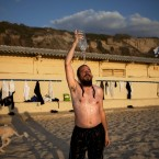 An ultra-Orthodox Jewish man takes an alternative shower at a gender-segregated beach in Tel Aviv, Israel (AP Photo/Oded Balilty)