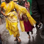 An Indian girl covers herself with her mother's sari during heavy rains in Dharmsala, India (AP Photo/Kevin Frayer)