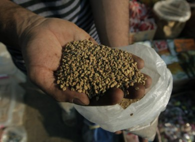 An Egyptian spice dealer displays fenugreek seeds at his shop in Cairo, Egypt
