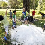Enjoying a snowball fight with ice shavings delivered from an indoor ice-hockey arena in Andover, Massachusetts. (AP Photo/Elise Amendola)