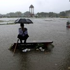 A security guard sits under an umbrella during monsoon rains in New Delhi, India. (AP Photo/Manish Swarup)