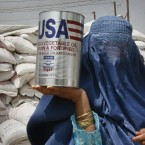 A woman carries an oil tin donated by the World Food Program in Kabul, Afghanistan. (AP Photo/Ahmad Nazar)