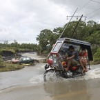 Motorists pass by a car which was washed downstream as they negotiate a flooded road in Legazpi city, Philippines. (AP Photo)