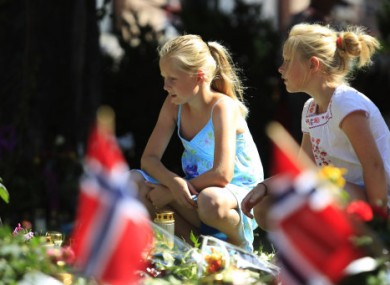 Oslo: Children sit by floral tributes left in memory of the victims of the 22 July bomb and gun attacks.