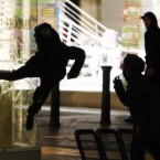 People kicking a jewellery shop window in Birmingham last night. (David Jones/PA Wire)