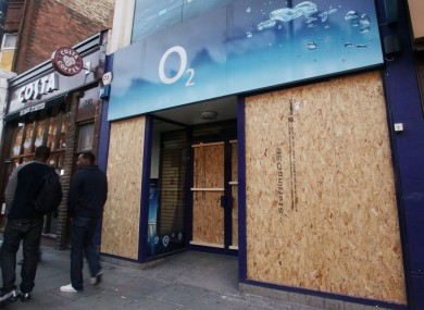 An o2 shop is boarded up after being looted in last week's riots in London.