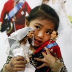Abbey Chan from Malaysia holds the dolls (AP Photo/Alastair Grant)