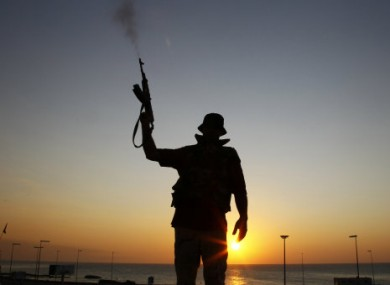 A Libyan rebel shoots in the air at a checkpoint in the Bab El Bahrah district in Tripoli yesterday.