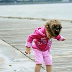 Emily Foley, 2, of Washington, makes a splash in a puddle while walking with her parents along the Potomac River, not far from the near the Kennedy Center, background, in the Georgetown section of Washington (AP Photo/Cliff Owen)