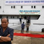A North Korean man waits as workers put up a banner reading,