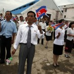 North Koreans wave flags to send off the North Korean leisure boat the