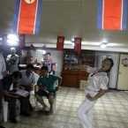 A waitress dances as a North Korean man sings karaoke during a trial cruise of the North Korean leisure boat the