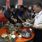 North Koreans and Chinese travel agents eat at a buffet during the trial cruise of the