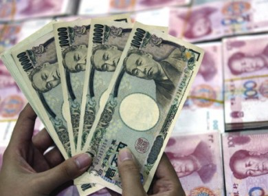 A bank clerk counts Japanese Yen banknotes over RMB (renminbi) yuan banknotes.