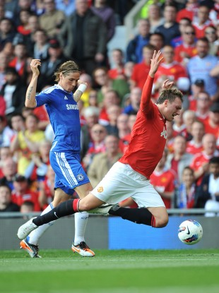 United's Phil Jones fall foul of Fernando Torres.
