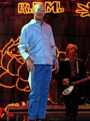 R.E.M. frontman Michael Stipe with Peter Buck in the background during the 1999 Glastonbury Festival.