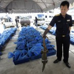 A Thai customs official displays one of 1,800 seized Bengal monitor lizards smuggled on pickup trucks to the capital from south of Thailand during a press conference at the customs headquarters in Bangkok, Thailand, Friday, April 8, 2011. Customs Department chief suspects the lizards were destined to be eaten. He said their meat sells for US.50- per pound (US- per kilogram) in China, making them worth more than US,000. (AP Photo/Sakchai Lalit)
