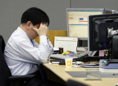 A trader at the foreign exchange room of the Korean Exchange Bank in Seoul reacts to Friday's trading.